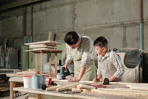 ワークショップで息子に板を挽く方法を見せながら、研磨機を使ってエプロンに集中した中年の大工