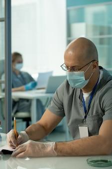 テーブルに座って患者の記録を埋める首にバッジを身に着けているマスクと手袋の集中中年医師