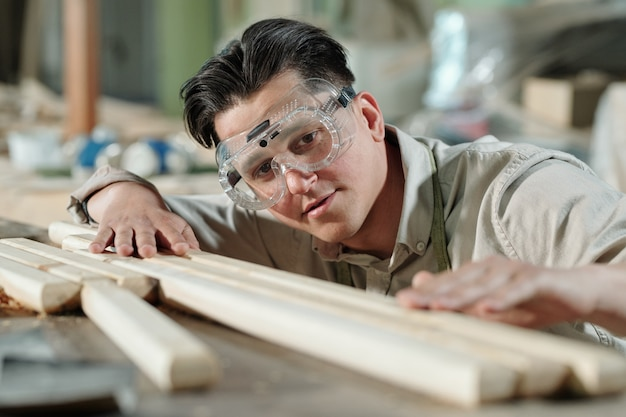 Concentrated middle-aged male carpenter in safety goggles examining surface of wooden planks in workshop