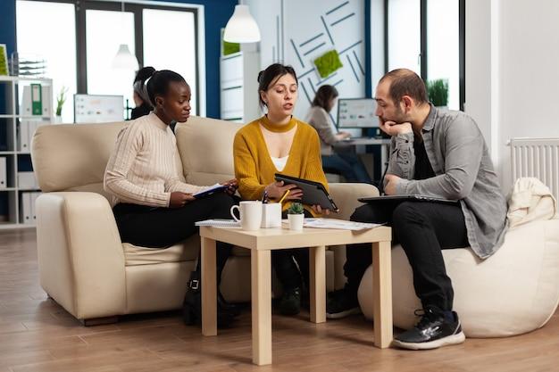 현대 시작 비즈니스 사무실에서 소파에 앉아 태블릿에서 연간 재무 보고서를 읽고 집중된 다민족 기업인