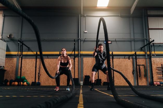 Сосредоточенные мускулистые мальчик и девочка выполняют интенсивные силовые упражнения в тренажерном зале с черной веревкой весом 20 кг.