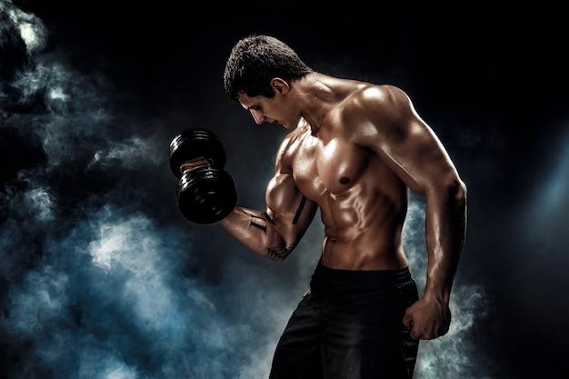 Концентрированный мускулистый мужчина делает упражнения с гантелями