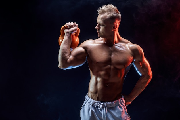 Concentrated muscular man doing exercise with kettlebell