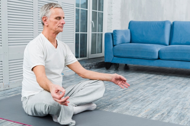 Concentrated old man meditating on mat at home