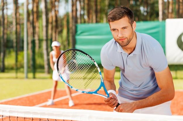 게임에 집중합니다. 테니스 라켓을 들고 테니스 코트에 서서 여자와 함께 뒤를 바라보는 잘생긴 청년