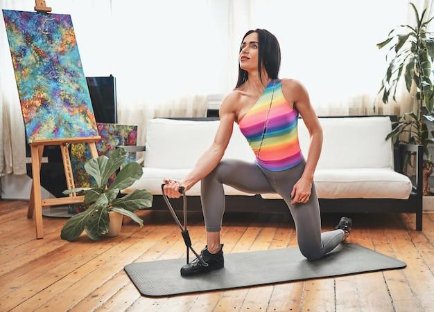 彼女のトレーニングに集中している中年のスポーツウーマンは、自宅のマットの上で運動しているカメラでポーズをとります。スポーツライフスタイルとボディケア。