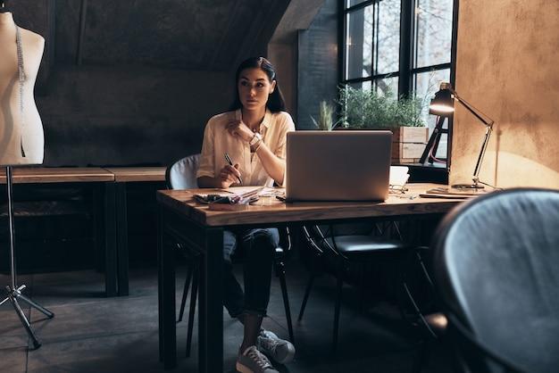 仕事に集中。彼女のワークショップに座ってスケッチに取り組んでいる美しい若い女性