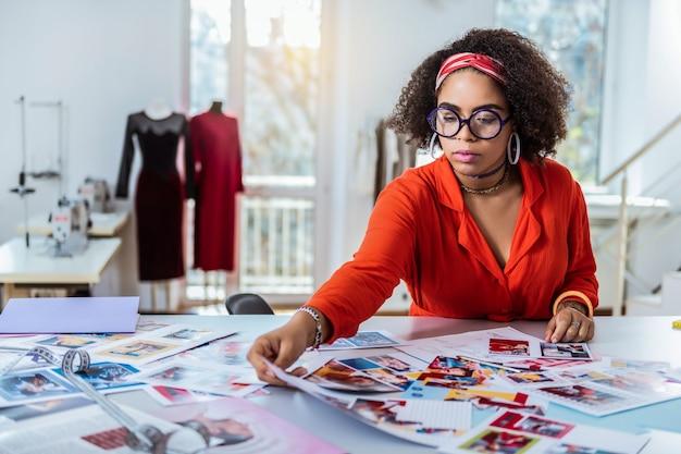 仕事に集中。彼女のテーブルの混乱から写真を選択する明るい衣装で忙しい格好良いブロンズの女の子