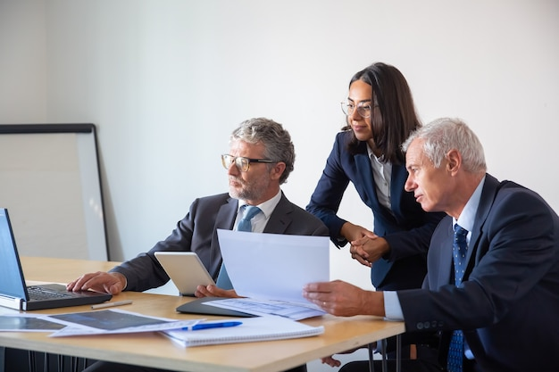 Сосредоточенные партнеры, использующие ноутбук и работающие с документами. уверенные серьезные бизнесмены в офисных костюмах обсуждают проект компании вместе. концепция управления, бизнеса и партнерства