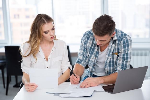 集中して物思いにふける女性と男性が仕事をし、プロジェクトについて話し合い、オフィスでノートパソコンを使う
