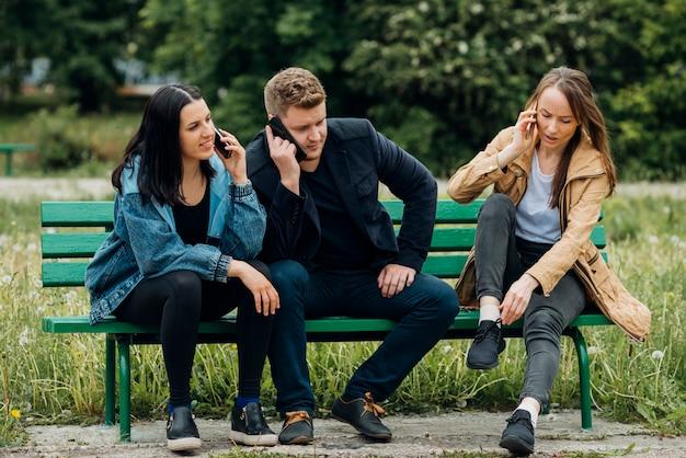 Сконцентрированные люди сидят на скамейке и разговаривают по мобильному телефону