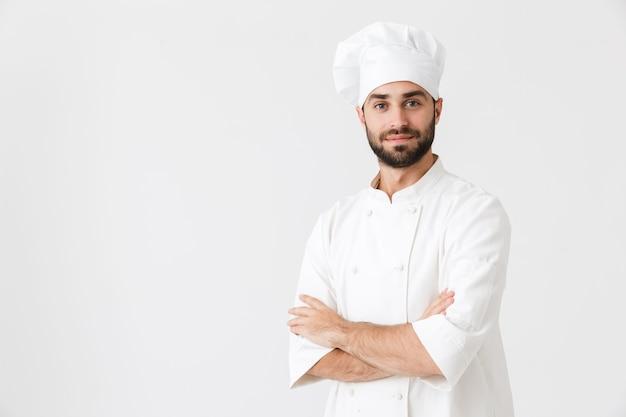 제복을 입고 포즈를 취하는 집중된 긍정적인 젊은 요리사.