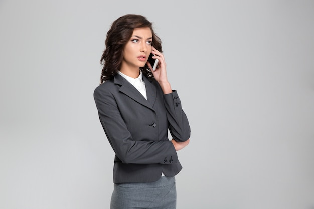 Concentrated pretty pensive curly young woman in gray costume talking on mobile phone