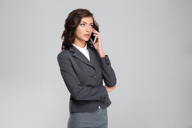 Сосредоточенная довольно задумчивая кудрявая молодая женщина в сером костюме разговаривает по мобильному телефону