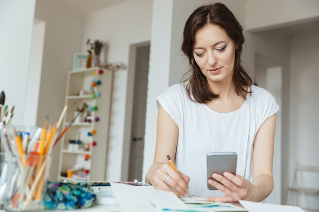 Концентрированная красивая женщина-художник рисует и использует смартфон в мастерской