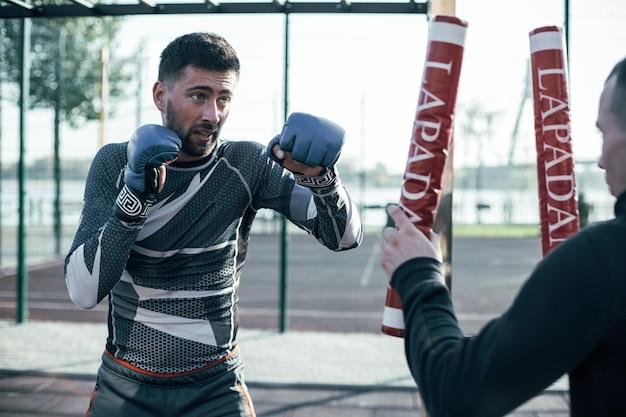 彼の前のボクシングスティックを見て、パンチの前に1つの拳を置く集中プロmmaボクサー