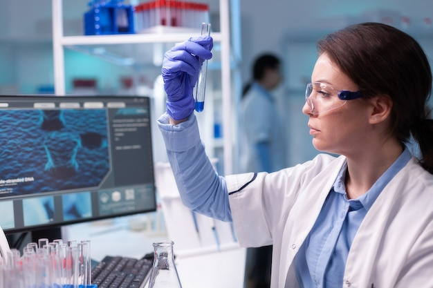 Concentrated professional woman scientist in laboratory working with test tube