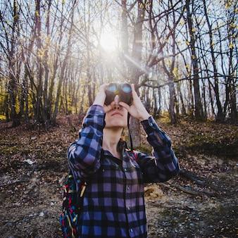 Concentrated rambler using her binoculars
