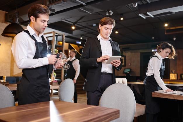 テーブルのオンラインレコードをチェックする集中レストランマネージャー