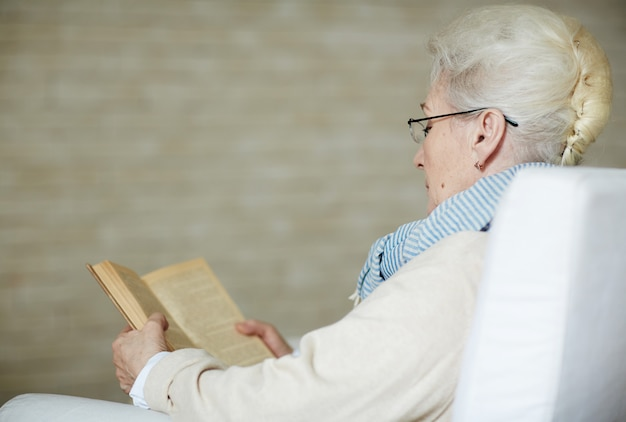 Concentrated retired woman reading old book