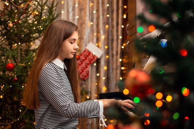 오래된 피아노에서 크리스마스 노래를 연주하는 집중된 학교 소녀