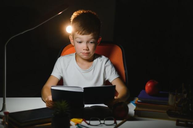 Концентрированный школьник читает книгу за столом с книгами, растением, лампой, цветными карандашами, яблоком и учебником