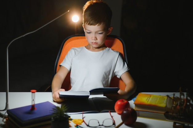 Concentrated schoolboy reading book at table with books, plant, lamp, colour pencils, apple, and textbook
