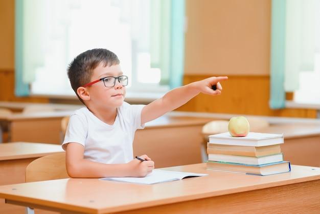 机に座って、後ろに座っているクラスメートと一緒に練習帳を書いている集中した男子生徒