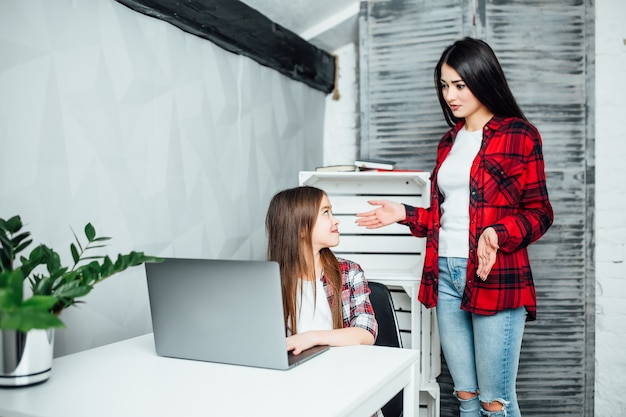 彼女を助けているラップトップの年上のsisrerで運動をしている間部屋に座っている集中した女子高生