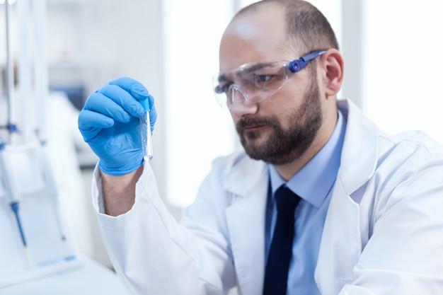 Сосредоточенный ученый в лаборатории, проводящей исследование образцов. исследователь биотехнологической стерильной лаборатории, держащей анализ в пробирке в перчатках и защитных очках.
