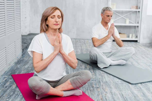 Concentrated senior couple performing yoga at home