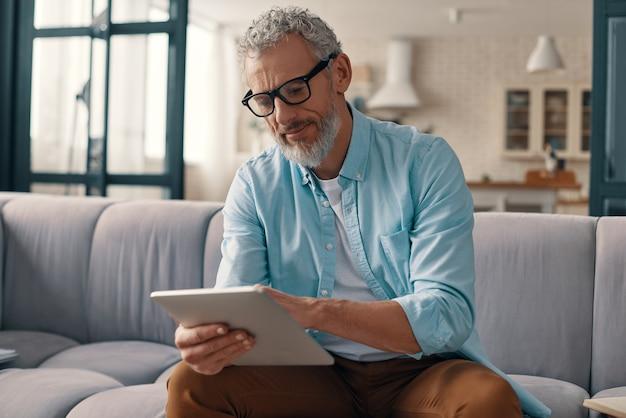 집에서 소파에 앉아있는 동안 디지털 태블릿을 사용하여 캐주얼 의류에 집중된 수석 남자
