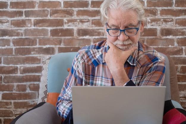 Сосредоточенный старший мужчина сидит дома на кресле с помощью портативного компьютера. кирпичная стена в фоновом режиме