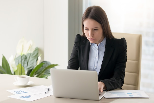 Concentrated serious businesswoman making report, working with laptop in office