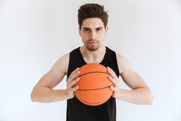 Concentrated serious strong young sports man basketball player holding ball isolated.