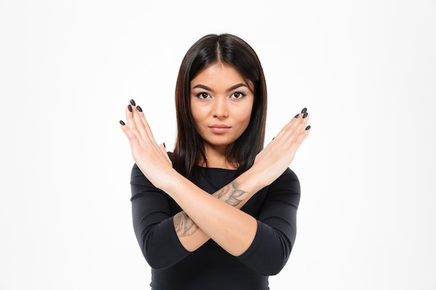 Concentrated serious young asian lady showing stop gesture