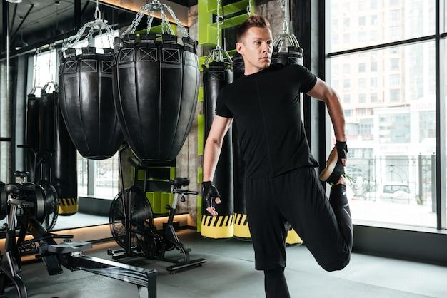 集中して深刻な若いスポーツマンはストレッチ体操を行います
