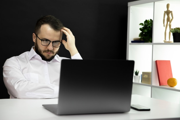 Concentrated sexy businessman working at laptop in modern home office. freelance