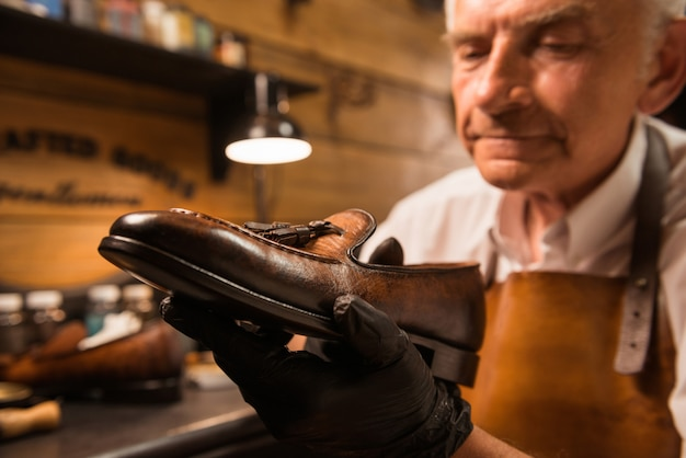 Concentrated shoemaker in workshop making shoes