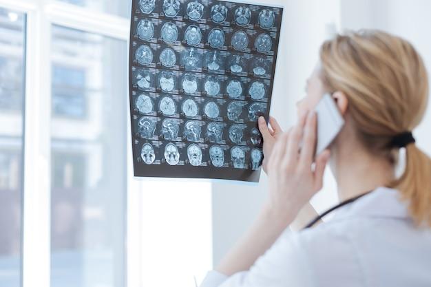 뇌 엑스레이를 들고 대화를 위해 전자 장치를 사용하면서 엑스레이 캐비닛에서 일하는 숙련 된 숙련 된 방사선 전문의