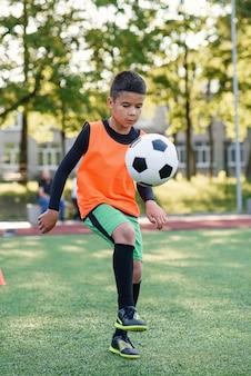 Сосредоточенный опытный футболист-подросток набивает футбольный мяч на ноге.