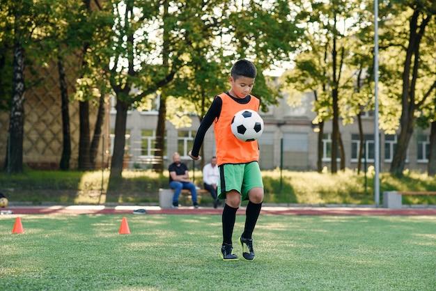 Сосредоточенный умелый подросток-футболист