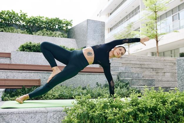Концентрированная стройная молодая женщина делает вариацию позы йоги дикой природы на открытом воздухе