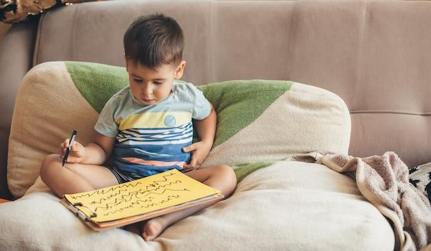 マーカーを使用して黄色い紙に描く集中した小さな男の子がベッドでポーズをとっています