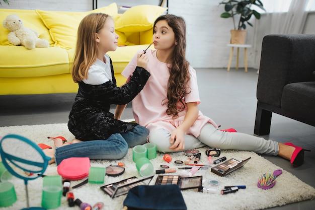 왼쪽에 작은 소녀가 집중되어 친구의 입술에 립스틱을 바르십시오. 그들은 방에있는 카펫에 함께 앉아 있습니다. 갈색 머리 소녀 포즈입니다.