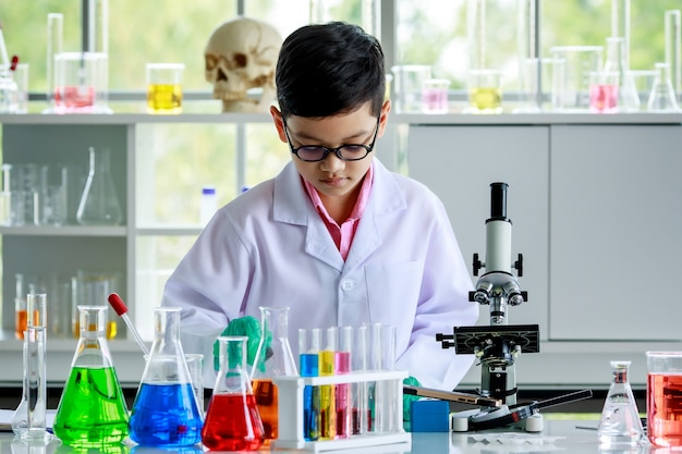 Concentrated smart asian boy in lab coat and gloves with dropper pouring liquid sample under microscope lens while conducting experiment during chemistry research in school laboratory.
