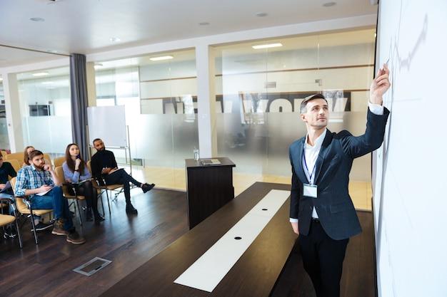Концентрированный спикер делает презентацию в конференц-зале и указывает на график на экране