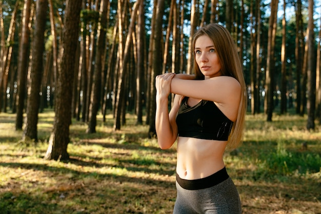Concentrated sportive girl in black tank top doing stretching exercises for arms, workout