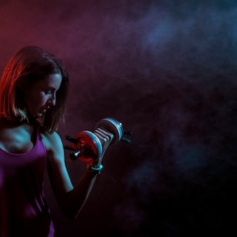 Concentrated sportive woman with dumbbell