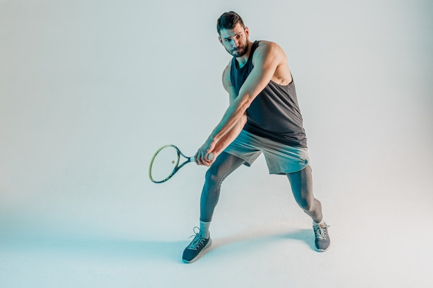 Concentrated sportsman hold racquet and play tennis. young bearded european tennis player. isolated on turquoise background. studio shoot. copy space
